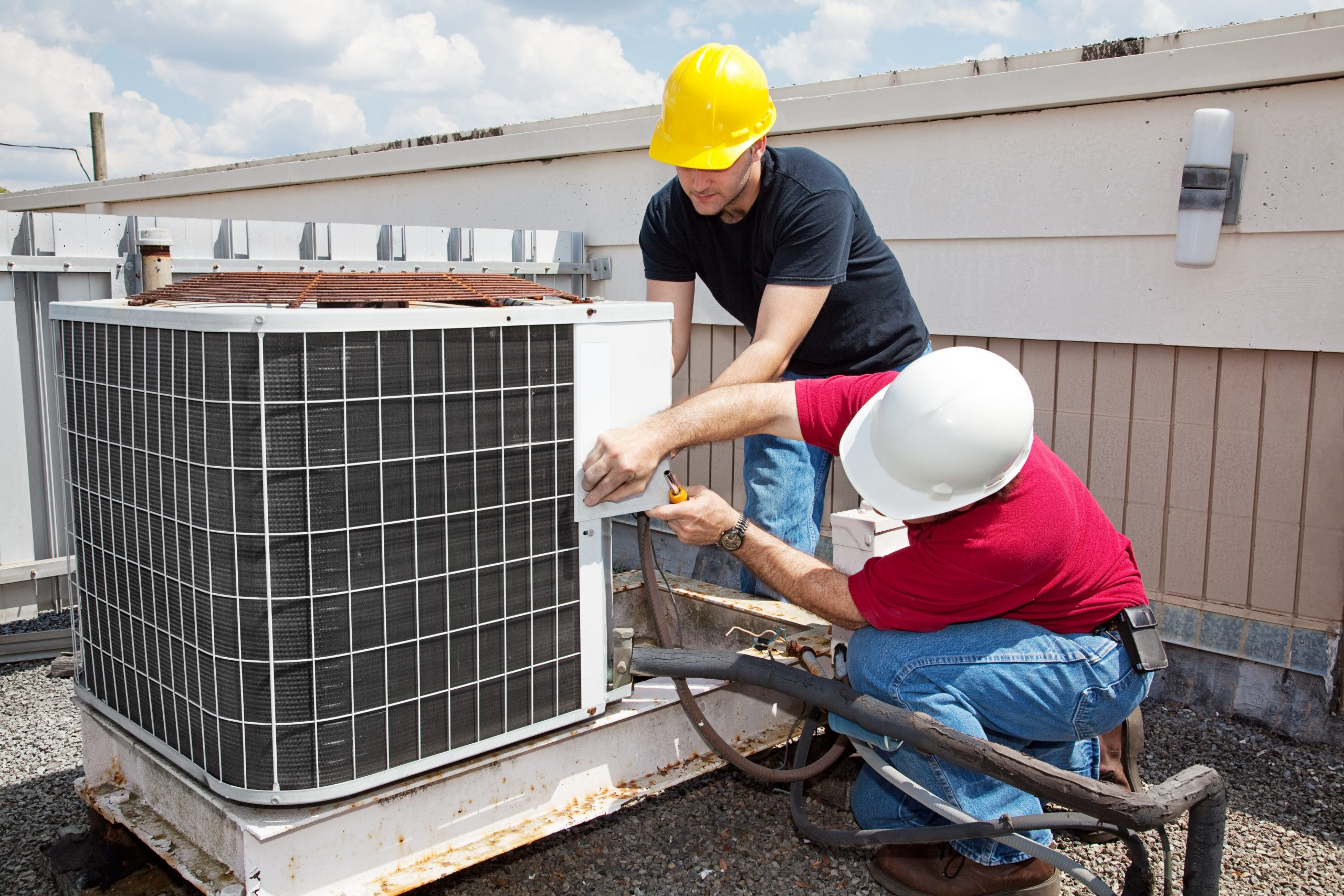 wo workers on the roof of a building working on the air conditioning unit.